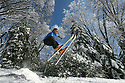 Under a canopy of winter-frosted forest Jonathan Thomas of Escondido goes airborne off a small jump he built on Palomar Mountain in 2009.  photo for North County Times