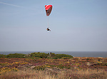 Parasailing over Dunwich Heath, Suffolk, England. Using thermals rising from the cliff face beneath to glide along the coastline,