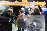 Joar Leifseth Ulsom recieves his winner's check from Kurt Parkan of sponsor Donlin Gold at the finish line in Nome, Alaska early on Wednesday morning March 14th as he wins the 46th running of the 2018 Iditarod Sled Dog Race.  He finished in 9 days 12 hours 00 minutes and 00 seconds<br /> <br /> Photo by Jeff Schultz/SchultzPhoto.com  (C) 2018  ALL RIGHTS RESERVED