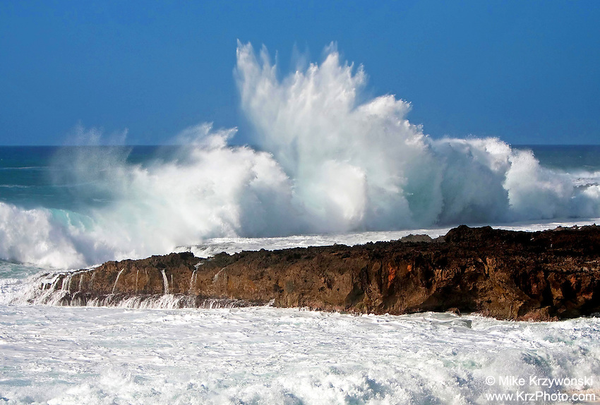 A large wave crashes on the rocks at Shark's Cove on the North Shore of Oahu