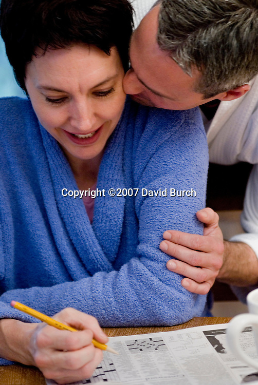 Mature couple solving crossword, he kissing her