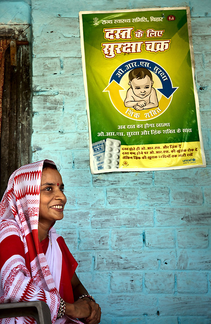 Chaurasia Anita who is an Anganwadi health worker beneath a sign advertising the benefits of oral rehydration salts (ORS) and zinc tablets at the local clinic on the porch of her residence in Rajasan Village. The village located in Vaishali district outside Patna in Bihar, India has been rolling out the ORS and Zinc program as part of the Ikea Social Initiative to combat child mortality rates caused by diarrhea. It is proving to be very successful with education and support provided by local nursing staff, health activists  and program officers from UNICEF. The treatment is a 14 day course administering diluted oral rehydration salts and a zinc tablet which is more effective than salts alone in combating the effects of severe diarrhea. Picture by Graham Crouch/UNICEF