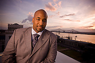 A man in a suit stands on a rooftop overlooking a large river.