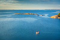 Ett par människor njuter av en roddtur med sin jolle på en stor fjärd i Stockholms skärgård. / A couple of people enjoying a boat trip with his dinghy on a large bay in the Stockholm archipelago.