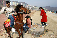 CHINA. Chongqing Province.  A man riding a horse in the town of Wushan on the Yangtze near to the 3 Gorges. The flooding of the three Gorges, by damming the Yangtze near the town of YiChang, has remained a controversial subject due to the negative environmental consequences and the displacement of millions of people in the flood plain. The Yangtze River however is reported to be at its lowest level in 150 years as a result of a country-wide drought. It is China's longest river and the third longest in the world. Originating in Tibet, the river flows for 3,964 miles (6,380km) through central China into the East China Sea at Shanghai.  2008.