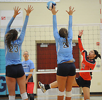 NWA Democrat-Gazette/ANDY SHUPE<br /> Erika Reaser (16) of Rogers Heritage sends the ball over the net as Emily Thompson (23) and Paige Williams (21) of Springdale Har-Ber defend Thursday, Sept. 17, 2015, at Wildcat Arena in Springdale. Visit nwadg.com/photos to see more photographs from the game.