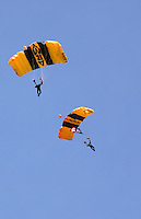 The Army Golden Knights parachute into the drop zone of the Dayton Airshow against a clear blue sky