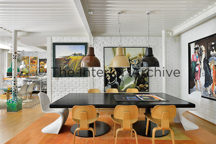 An open-plan space with a painted beamed ceiling and brick walls and a wood floor. In a dining area, three pendant lights hang above a black table set around with Eames and Arne Jacobsen chairs.