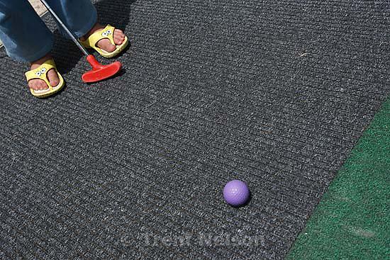 Kaysville - at Cherry Hill Tuesday June 9, 2009. .Garrett Frazier and Ciera McFarland miniature golfing. mini golf. spongebob squarepants sandals