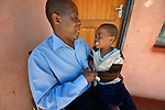 Sunny Nyamandwe (left) talks with his 4-year old grandson Sunny at his home in Ruwa, Zimbabwe. Nyamandwe works at the National Rehabilitation Centre in Ruwa, which assembles and fits wheelchairs provided by the Jairos Jiri Association with support from CBM-US. Nyamandwe is one of the beneficiaries of the program. His legs remain paralyzed after an automobile accident more than two decades ago.