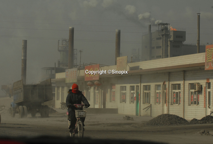 Locals cover their faces as they pass a coal power station and coking plant that spews carbon monoxide and sulphur dioxide in Linfen, Shanxi Province, China. China produces around 2.4 billion tones of coal annually that contributes to more than 400,000 premature deaths annually due to air pollution, acid rain and poisonous ground water. Linfen is reportedly the most polluted city in China...PHOTO BY SINOPIX