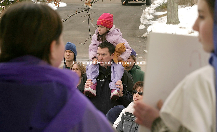 SOUTHBURY, CT- 25 MARCH 2005-032505J12---Chris Dembski of Southbury and his daughter Sydney Dembski, 5, watch the annual Good Friday Faith Walk sponsored by Southbury churches. The event, which dramatizes the Stations of the Cross, finished at the Sacred Heart Church in Southbury. -- Jim Shannon Photo--Good Friday Faith Walk; Southbury; Jesus; Sacred Heart Church, Chris Dembski, Sydney Dembski are CQ