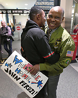 NWA Democrat-Gazette/J.T. WAMPLER John Feruzi greets his uncle Watata Mwenda (RIGHT) Tuesday March 20, 2018 at the Northwest Arkansas Regional Airport in Highfill. Feruzi spent years in a refugee camp in Malawi after fleeing his native Republic of the Congo.