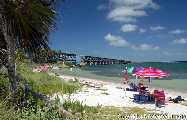 view of Caloosa Beach at Bahia Honda State Park, Fl. Keys.  Bright red beach umbrella on sand, the old Flagler RR trestle bridge in background, bathers in water