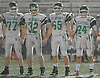 Seaford teammates, from left, No. 77 Kevin Digney, No. 32 Frank Lauretti, No. 65 Nick Kocienda and No. 24 Thomas Sabatino line up before the coin toss in the Nassau County varsity football Conference IV final against Locust Valley at Hofstra University on Thursday, Nov. 19, 2015.<br /> <br /> James Escher