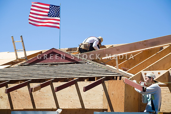 Two construction workers beside an American flag working on a roof of a single family home construction site. Los Altos, California, USA