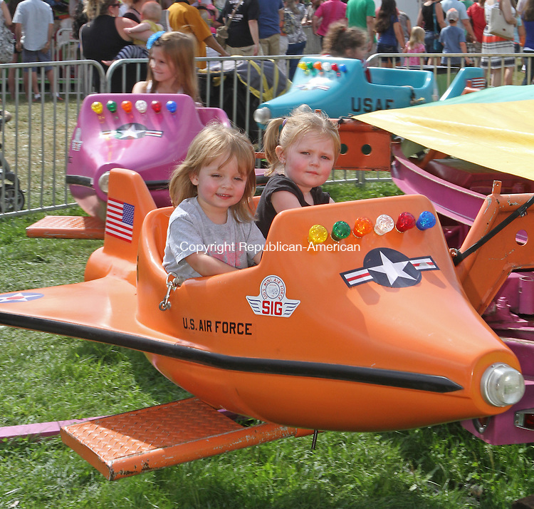 Bridgewater, CT-081713MK20 (from left) Olivia Popilowski and Linneah Brennan ride in a space plane as hundreds of spectators enjoyed the warm sunny weather during the 62nd annual Bridgewater country fair Saturday afternoon.  The fair continues today with events beginning at 9 AM.  Michael Kabelka / Republican-American