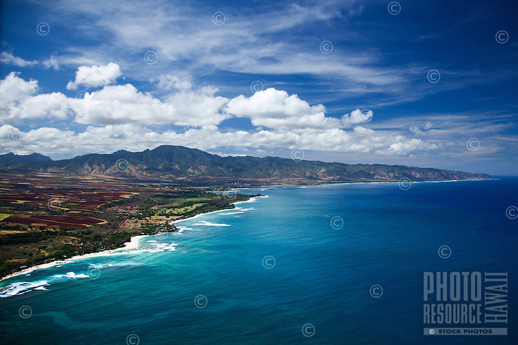 An aerial view of O'ahu's North Shore, with the Ko'olau Mountain Range and Ka'ena Point in the distance.