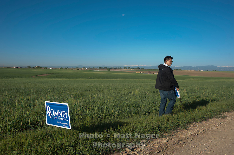James Garcia (cq) places signs before presumptive Republican candidate for President Mitt Romney (cq) speaks to a crowd at a K.P. Kauffman Company oil rig in Fort Lupton, Colorado, Wednesday, May 9, 2012. Romney was giving a recovering the economy stump speech.<br /> <br /> Photo by MATT NAGER