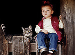 Young girl sitting in barn window with pet cat, San Luis Obispo, California.(Maddy with buck/MR)