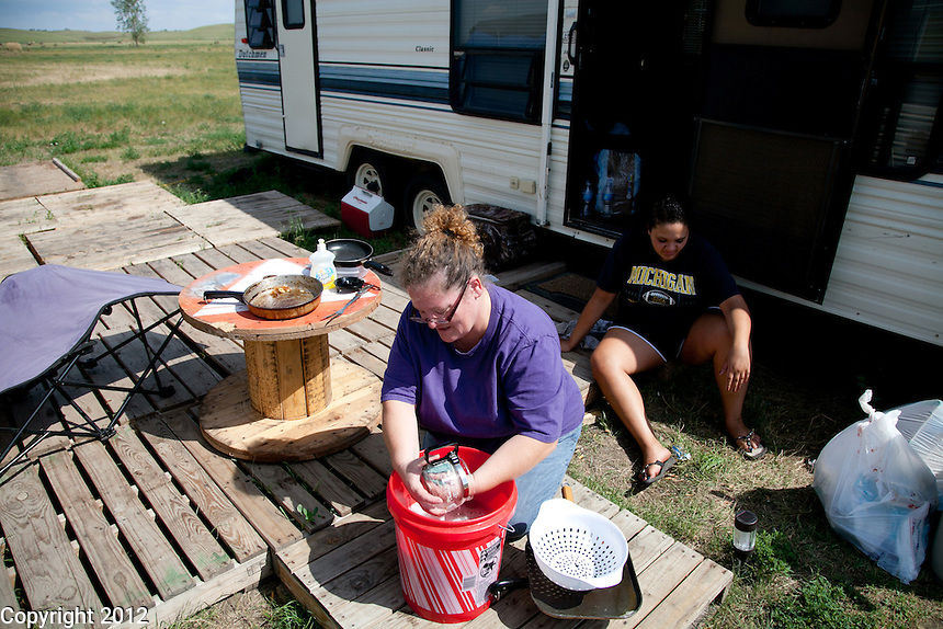 Wendy Bell does the dishes outside as the water in the trailer doesnt work.
