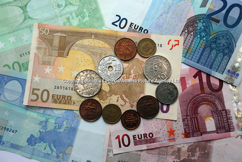 A mixture of old drachma coins surrounding the map of Europe on a 50 euro paper note<br />