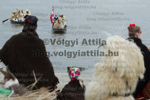 Local people in traditional buso dresses watch as others cross river Danube to celebrate the Buso Carnival in Mohacs, about 200 km south from the capital city Budapest on March 02, 2014. ATTILA VOLGYI