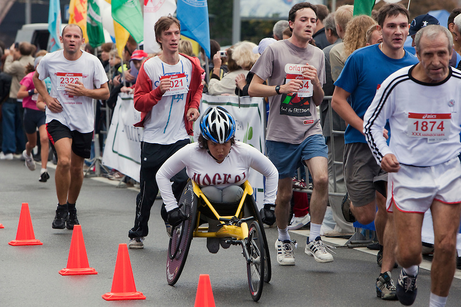 Moscow, Russia, 12/09/2010..Runners and a disabled contestant approach the finish line at the 30th annual Moscow International Marathon.