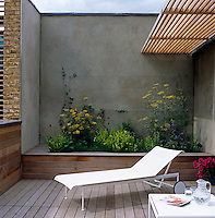 On the west-facing cedar deck an Italian sun lounger is situated in front of a raised herb bed