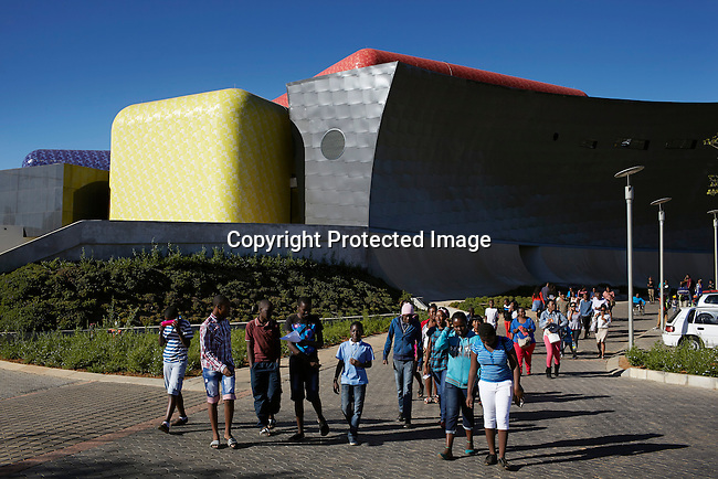 SOWETO, SOUTH AFRICA MAY 4: Visitors leave an art and craft market at the new Soweto theatre on May 4, 2013 in Jabulani section, Soweto, South Africa. The theatre is one of many new developments in the township and show plays, concerts and markets on different stages. Soweto today is a mix of old housing and newly constructed townhouses. The population in Soweto is estimated to be around one million people. A new hungry black middle-class is growing steadily. Many residents work in Johannesburg but the last years many shopping malls have been built, and people are starting to spend their money in Soweto. (Photo by: Per-Anders Pettersson)