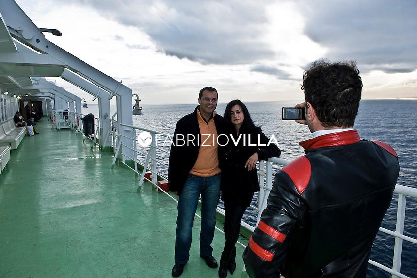 La nave traghetto Scilla della compagnia Bluvia, Ferrovie dello Stato, collega Villa San Giovanni con Messina trasportando passeggeri con auto al seguito e treni. Foto ricordo sulla Stretto di Messina per due giovani fidanzati.