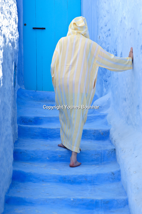 An old man wearing a yellow djellaba walks around the blue streets of Chefchaouen