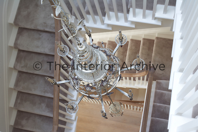 An ornate silver chandelier decorates the central stairwell