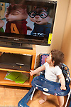 10 month old baby boy in stationary walker, looking at cartoon show on television