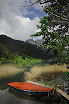 Rowing boat with orange protective tarpaulin. Lake Haldensee, Nesslewangle, Reutte district. Austria.The Alps