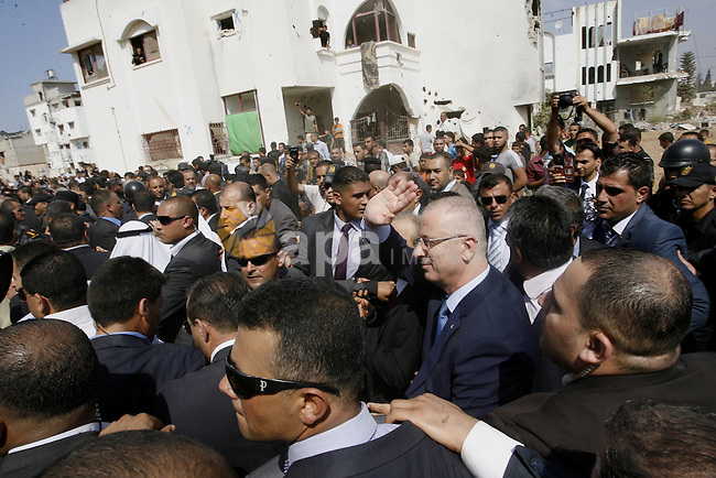 Palestinian Prime Minister Rami Hamdallah waves to residents as he visits the al-Shijaiyah neighborhood in the east of Gaza city on October 9, 2014. The Palestinian unity government which took the oath of office in June under technocrat prime minister Rami Hamdallah arrived to Gaza Strip on Thursday to convene the first fully meeting. Hamdallah said that the unity government will rebuild the bombed-out Gaza Strip following a seven-week Israeli offensive. Photo by Abed Rahim Khatib