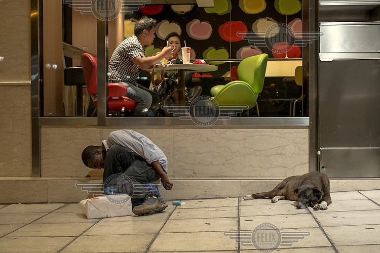 ATHENS, GREECE: an immigrant under the effects of narcotics at the doors of a Mc Donalds restaurant in Syntagma square.