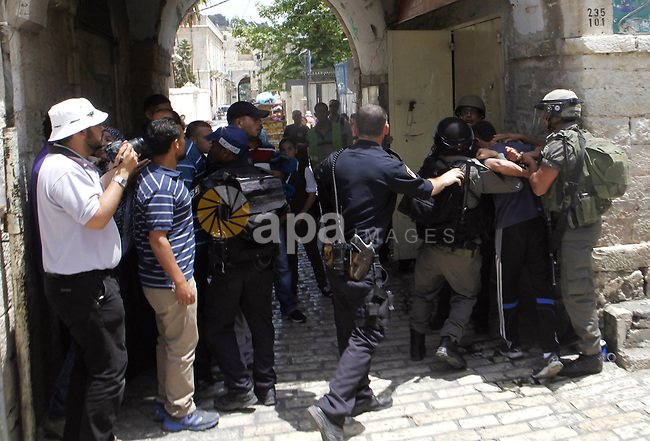 """A Palestinian man is arrested by Israeli security officers following a protest against Israelis celebrating Jerusalem Day on May 8, 2013 at the Damascus gate in Jerusalem's Old City. Jerusalem day marks the anniversary of the reunification of the holy city. Thousands of Israelis joined marches and rallies throughout the city, including a """"flag march"""" that passed through Damascus Gate on its way to the Western Wall. Police, who were deployed in their thousands, arrested 13 people including two """"Arab youths"""" suspected of throwing water at Jews participating in the flag dance near Damascus Gate, police spokeswoman Luba Samri said in a statement. Photo by Sliman Khader"""