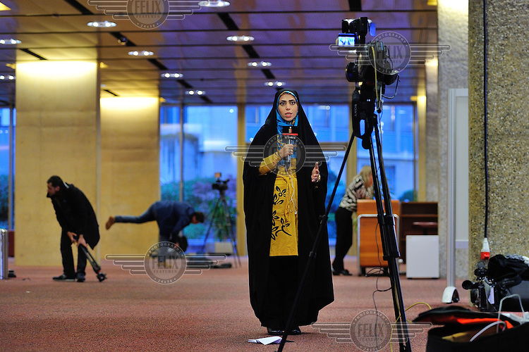 An Iranian state TV anchor woman wearing Islamic dress speaks to camera at the press centre during the the E3 / EU+3 Iran talks. <br /> <br /> The E3 / EU + 3 talks, which include the UK, France and Germany plus the USA, China and Russia are intended to discuss Iran's nuclear programme which Iran insists is intended for civilian purposes only while some governments in the West suspect it of having the building of a nuclear weapon as its ultimate goal.