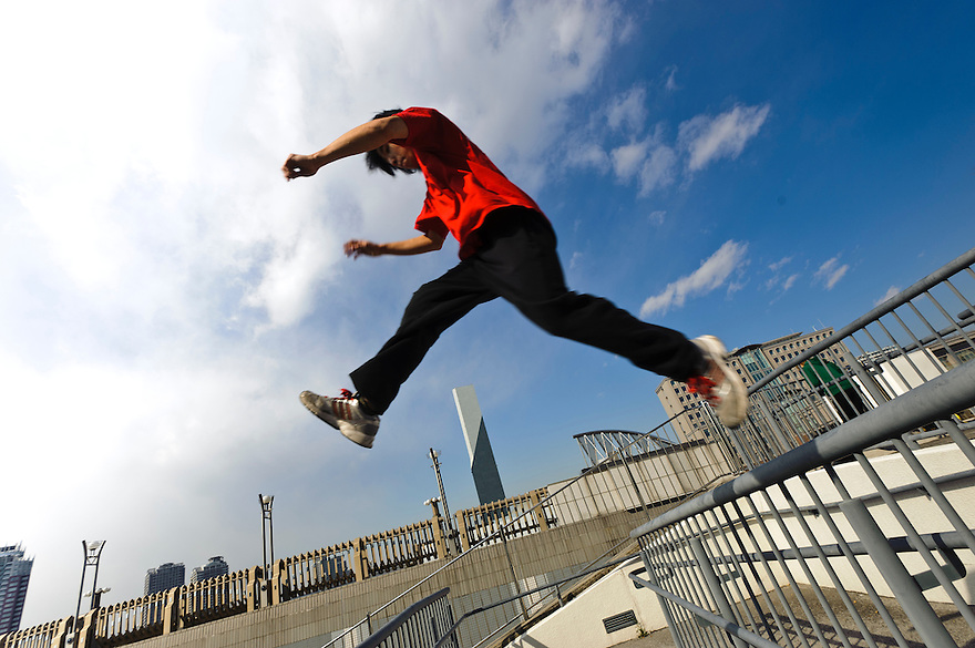 """Traceur (parkour practitioner) """"Yutaro"""". Practicing Parkour in Odaiba, Tokyo, Japan, January 27, 2012. Parkour is a modern method of physical training, also known as freerunning. It was founded in France in the 1990s. There is a small group of around 50 parkour practitioners in Tokyo."""
