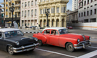 Havana, Cuba - Taxis on the Malecón road facing Havana Bay. Classic American cars from the 1950s, imported before the U.S. embargo, are commonly used as taxis in Havana.