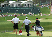 Bethesda, MD - July 4, 2007 -- Tiger Woods (center), watches as Sergeant Major Mia Kelly prepared to tee off from down hill during the inaugural Earl Woods Memorial Pro-Am Tournament, part of the AT&T National PGA Tour event, Wednesday, July 4, 2007, at the Congressional Country Club in Bethesda, Maryland.  Kelly was one of two service members who participated in a foursome with Tiger Woods in the event honoring soldiers and military families. .Credit: Molly A. Burgess - DoD via CNP    .