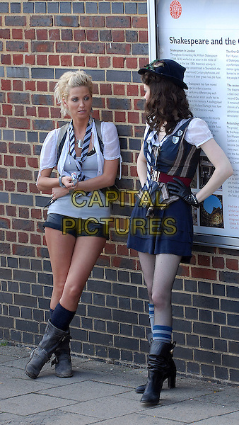 "SARAH HARDING & TALULAH RILEY.Filming on the set of ""St Trinian's: The Legend of Fritton's Gold"", outside the Globe Theatre, London, England..August 10th, 2009.2 full length black mini micro shorts grey gray top white shirt scarf striped stripes biker boots girls aloud waistcoat beige socks hat gloves film movie uniform leaning against wall profile.CAP/IA.©Ian Allis/Capital Pictures."