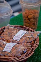 A bag of almonds for sale, with a cup of almonds for taste-testing behind them.