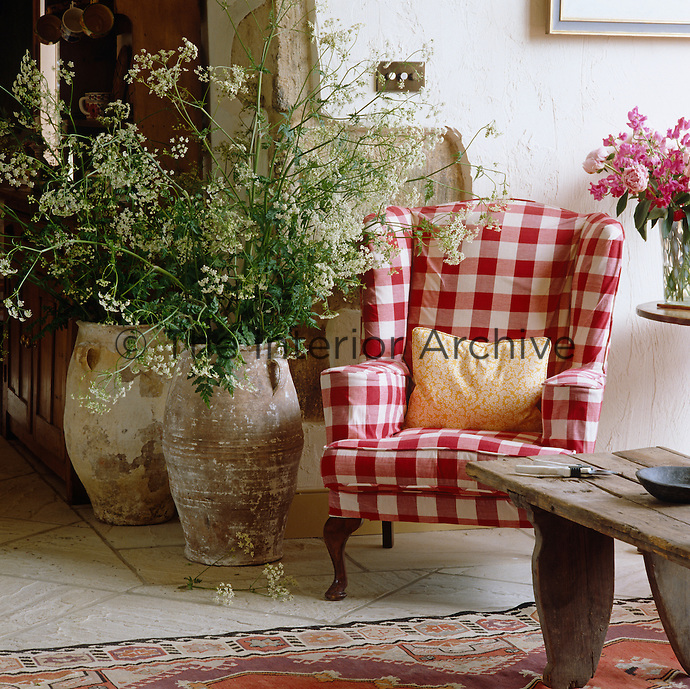 A wing-backed armchair in the living room, upholstered in red and white gingham, is placed next to two large earthenware urns filled with cow parsley