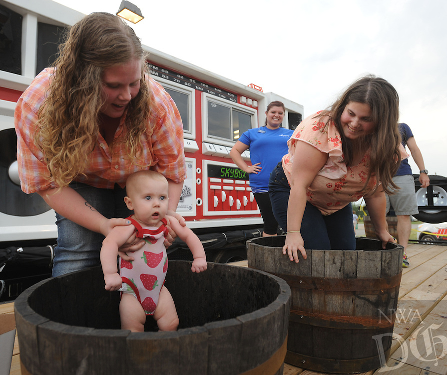 NWA Democrat-Gazette/ANDY SHUPE<br /> Dakota McCawley (left) holds her 7-month-old daughter, Kambrie, Tuesday, Aug. 4, 2015, as she and Christian Reed (right), all of Fayetteville, stomp grapes during the 117th annual Tontitown Grape Festival. The festival continues through Saturday. Visit nwadg.com/photos to see more photographs from the festival.