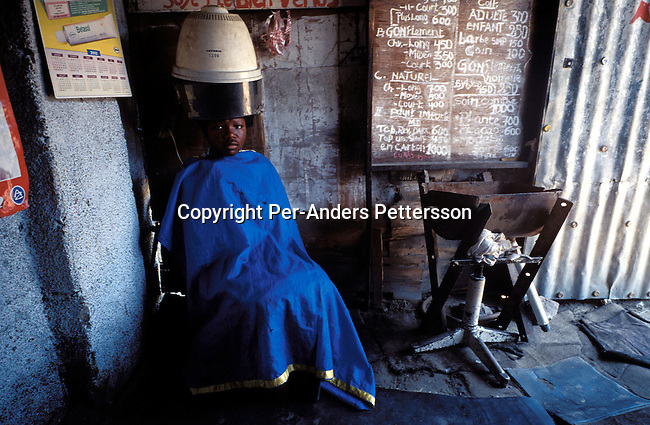 KINSHASA, CONGO - FEBRUARY 29: Perpeture Tulubeli, age 15, gets her hair done in a hair saloon in a wooden shack on February 28, 2002 in central Kinshasa, Congo. She wants to look nice and proper, and goes to the saloon regularly. Mpindi Eariste, the owner is catering both to women and men. A straight haircut is about 300 Congolese Francs, about $1..Photo: Per-Anders Pettersson/ Getty Images...