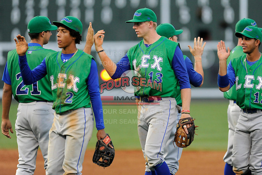 Shortstop Raul Mondesi (2) and third baseman Hunter Dozier (13) of the Lexington Legends high-five teammates after beating the Greenville Drive 5-0 on Friday, August 18, 2013, at Fluor Field at the West End in Greenville, South Carolina. Mondesi is the No. 5 prospect of the Kansas City Royals. (Tom Priddy/Four Seam Images)
