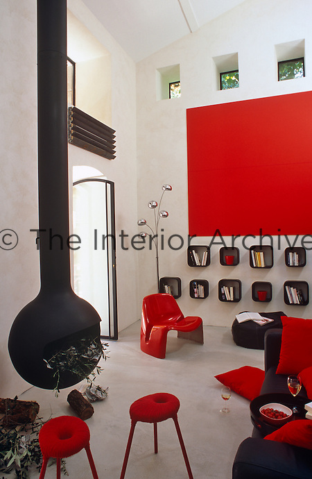 A modern black bulbous wood burning stove is suspended in the centre of the red, white and black living room