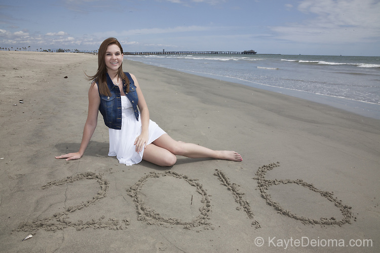 Portrait of a teenage girl on the beach with the year 2016 in the sand